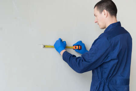 electrical worker performs marks on the wall for the installation of sockets