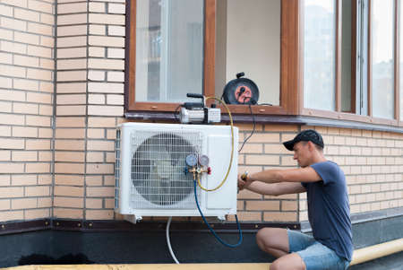 the worker installs the outdoor unit of the air conditioner on the wall of the house