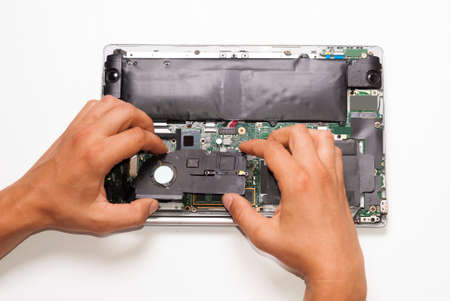 repairman installs cooler on laptop processor
