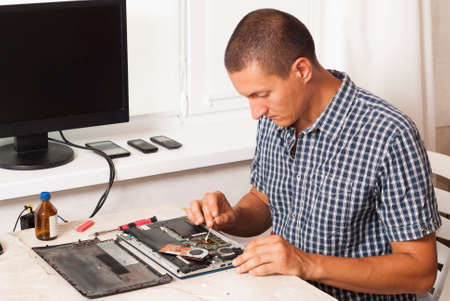 repairman cleans laptop processor from old thermal paste