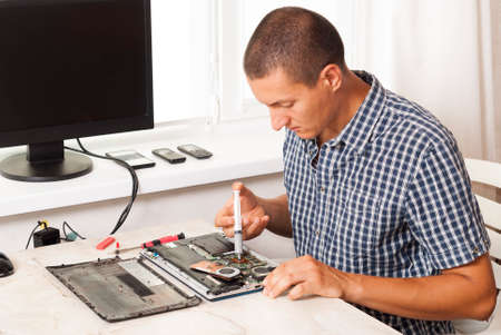 repairman applies thermal paste to laptop processor
