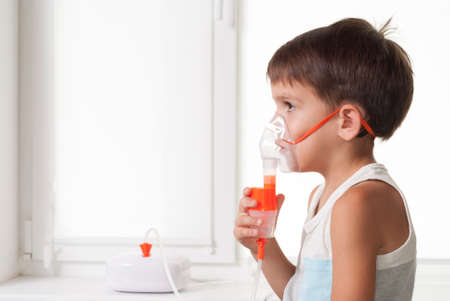 the child inhales medicine through an inhaler