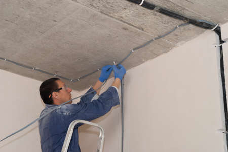 worker attaches electric cable to concrete ceiling indoors 스톡 콘텐츠