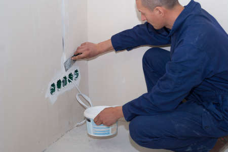 electrician installs socket boxes on the wall and puts a putty on them 스톡 콘텐츠