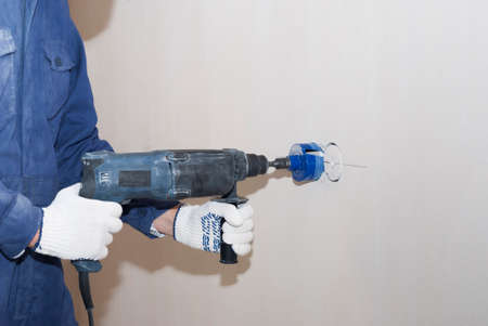 an electrician uses a diamond bit for drilling reinforced concrete 스톡 콘텐츠