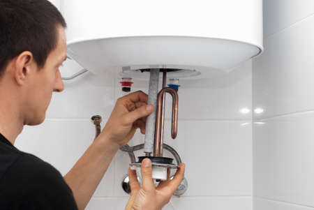 master installs a new electric heating ten in a water tank
