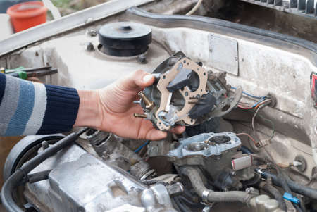 the repairman replaced the gasket in the carburetor and installs it in place 스톡 콘텐츠