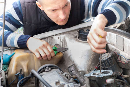 car mechanic holds a screwdriver and adjusts carburetor 스톡 콘텐츠