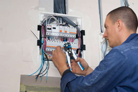 electrician connects wire to automatic fuse device