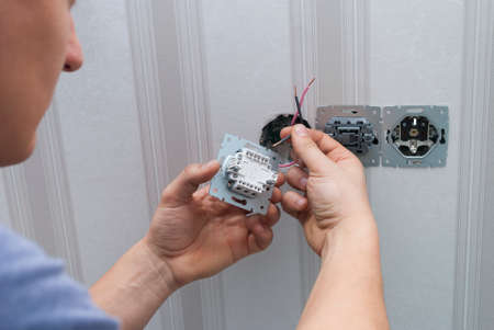 worker installs an lighting switch in the house