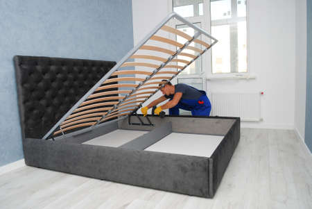 the master is assembling a new bed with a lifting mechanism in the buyer's apartment