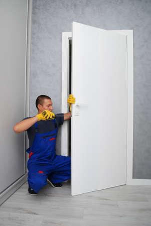 the worker with screwdriver is repairing a door lock