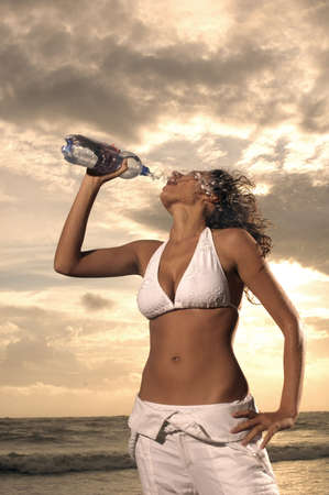 Woman drinking water on the beach photo