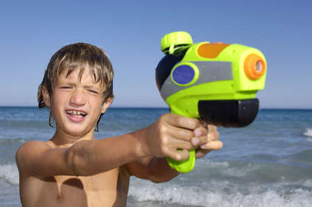 Young boy playing with water gun