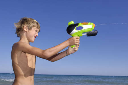 water gun: Young boy playing with water gun