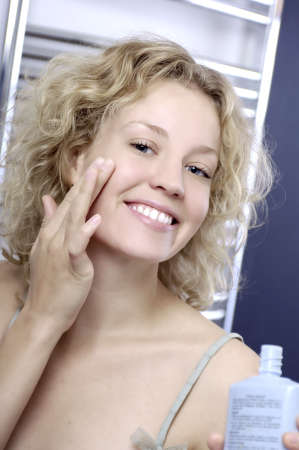 smiling woman using face cream Stock Photo - 8030117