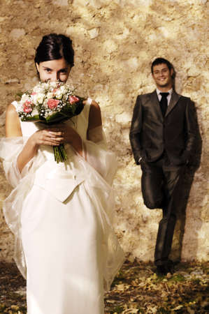 bruid met bloemen en bruidegom die achter