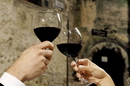 two hands holding glasses of red wine Stock Photo - 8420872