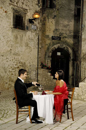 cena romantica: giovane coppia bere vino rosso Archivio Fotografico