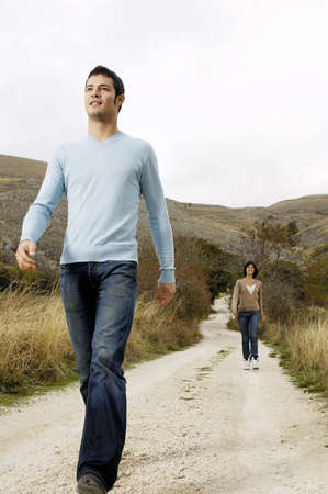 Man walking on a country path with woman behind Standard-Bild