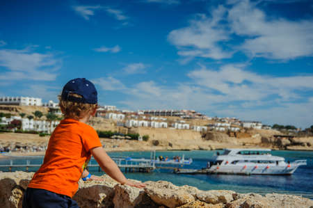 tropica: boy child is looking from the mountain to the beach with blue sea and nice boat yacht