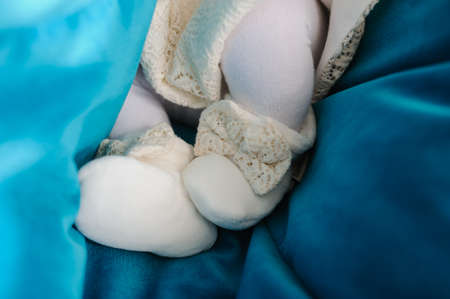 Knitted white baby shoes for girl on a blue background