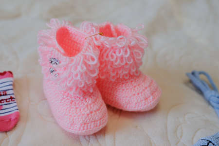Knitted pink baby shoes for girl on a white background
