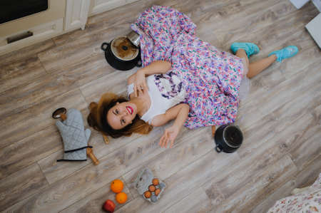 young woman lying on the floor in a vintage kitchen very sad. orange, eggs, apples, flour around her Stock Photo