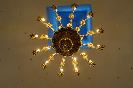 Gold plated vintage chandelier hanging on the ceiling