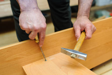 Worker Repairing Furniture With Screwdriver And Hammer. View Of Hands Photo