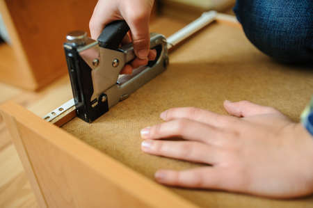 engrapadora: Worker repairing furniture with industrialconstruction stapler