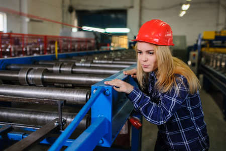 Portret of nice beautiful woman in red safety helmet at metal tile roof manufacturing factory examine the forming process Stock Photo