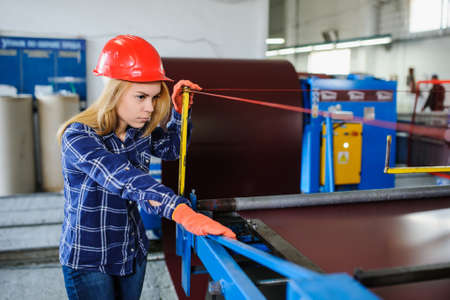 the emancipation: Portret of nice beautiful woman in red safety helmet at metal tile roof manufacturing factory examine the forming process Stock Photo