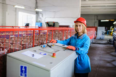 the emancipation: beautiful woman in red safety helmet work as industrial worker at metal sheet profiling mechine at manufacturing factory Stock Photo