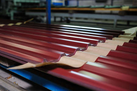 roof profile: Metal tile manufacturing factory. Steel sheet metal roll profiling forming machine with rolls in working process. Stock Photo
