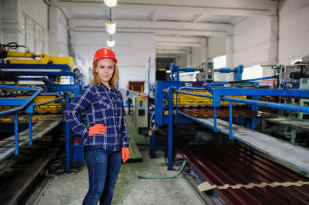 the emancipation: Portret of nice beautiful woman in red safety helmet at metal tile roof manufacturing factory