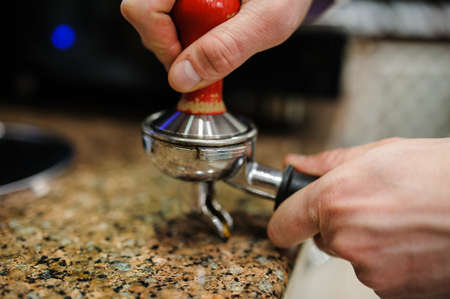 macchiato: Closeup barista grinding fresh coffee into bayonet.