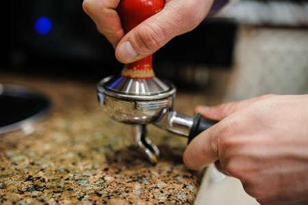Närbild barista slipning färskt kaffe i bajonett. Stockfoto