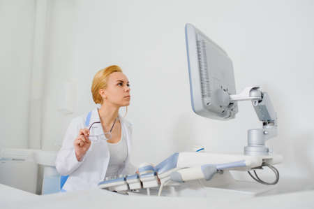 sonography: Young beautiful woman doctor working at ultrasound diagnostic machine usg and analyze the result