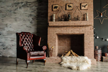 old brick wall: Vintage living room, retro style. Fur, leather armchair, fireplace, interesting bed with nice pillows and large windows Stock Photo