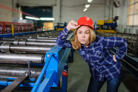 roof profile: Portret of nice beautiful woman in red safety helmet at metal tile roof manufacturing factory examine the forming process Stock Photo
