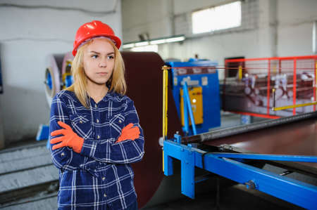 beautiful woman in red safety helmet work as industrial worker at metal sheet profiling mechine at manufacturing factory Stock Photo
