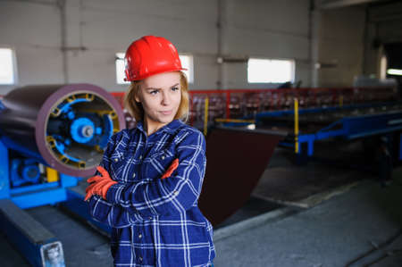 sheet metal: Portret of nice beautiful woman in red safety helmet at metal tile roof manufacturing factory