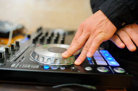 midi: Dj mixes the track in the nightclub at party