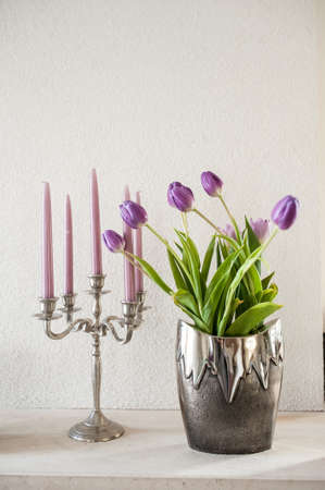 vintage decoration. violet tulips in silver metal vase and violet candles in metal candlestick