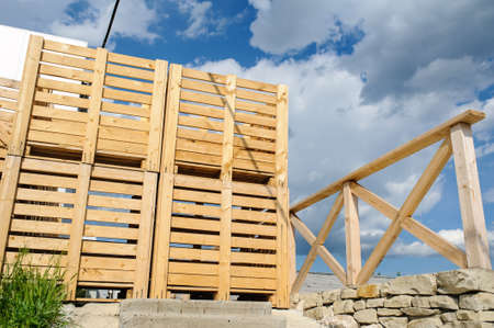 empty warehouse: Wood pallets arranged in row, and blue sky behind