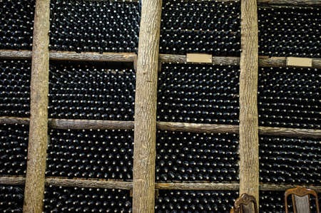 store shelf: Wine cellar with bottles on wooden shelves