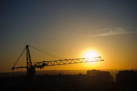 unfinished building: tower cranes silhouette at construction site in sunrise