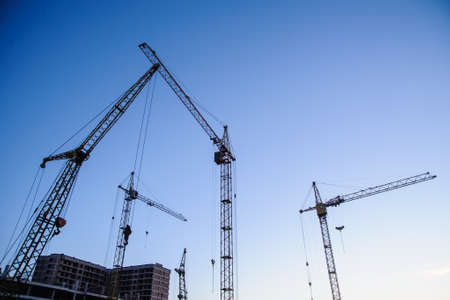 unfinished building: tower cranes silhouette at construction site on blue sky Stock Photo