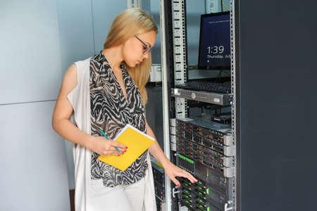 Jonge vrouw ingenieur IT-technicus met notitieboekje in de datacenter server kamer neemt notities over het probleem.
